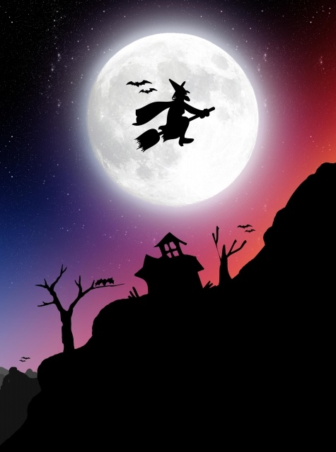 A witch flies past the full moon on halloween.